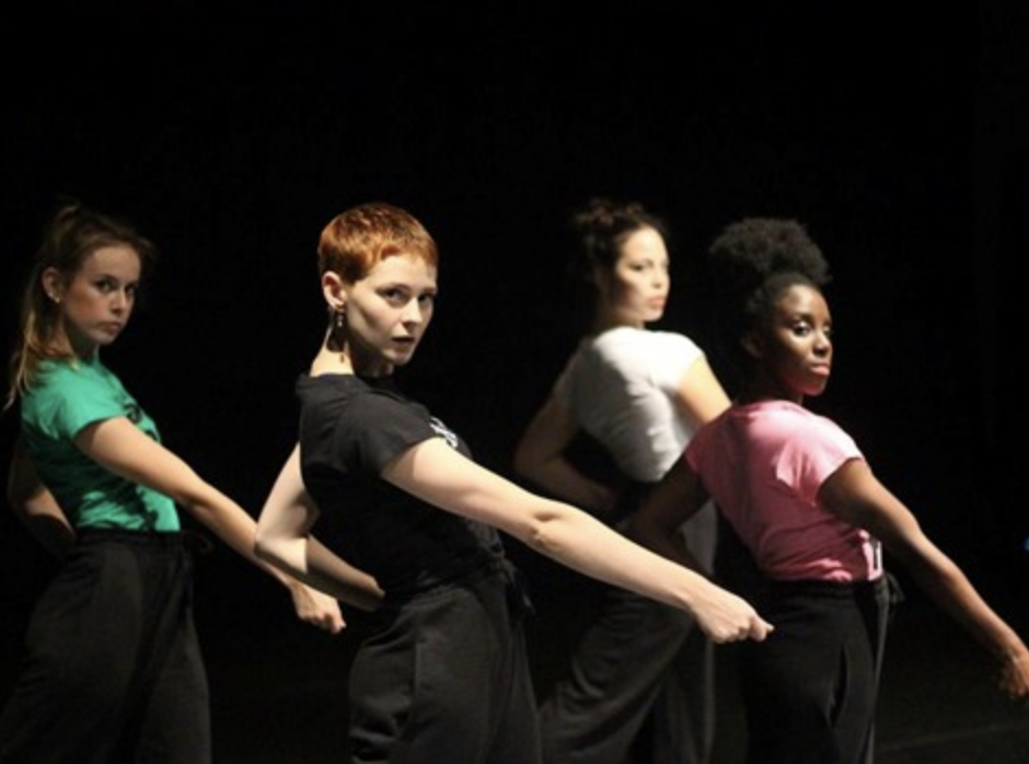 Four women contemporary dancers in staggered line all pointing with right arm diagonally to the ground whilst looking to camera and leaning back.