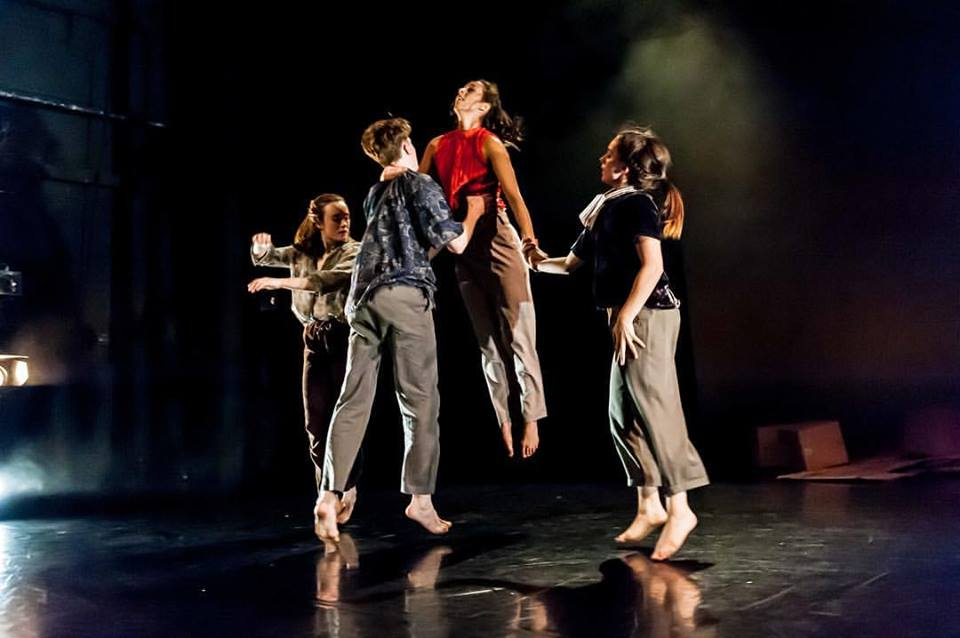 Four young contemporary dancers, one being lifted into the air. Black backdrop with stage lights.