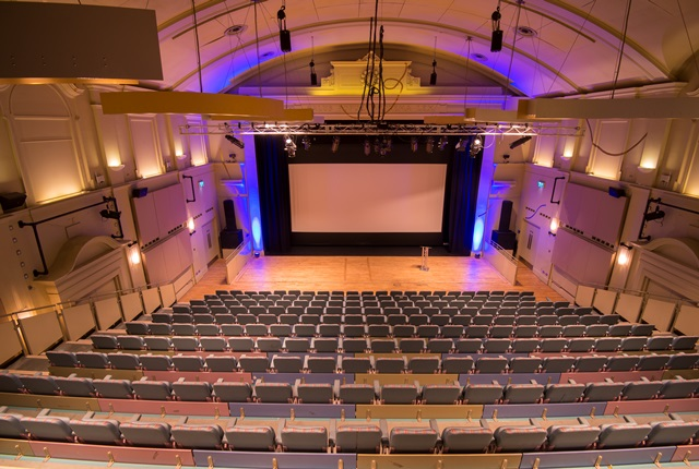 Aerial view of seating and stage in main auditorium from centre of back row