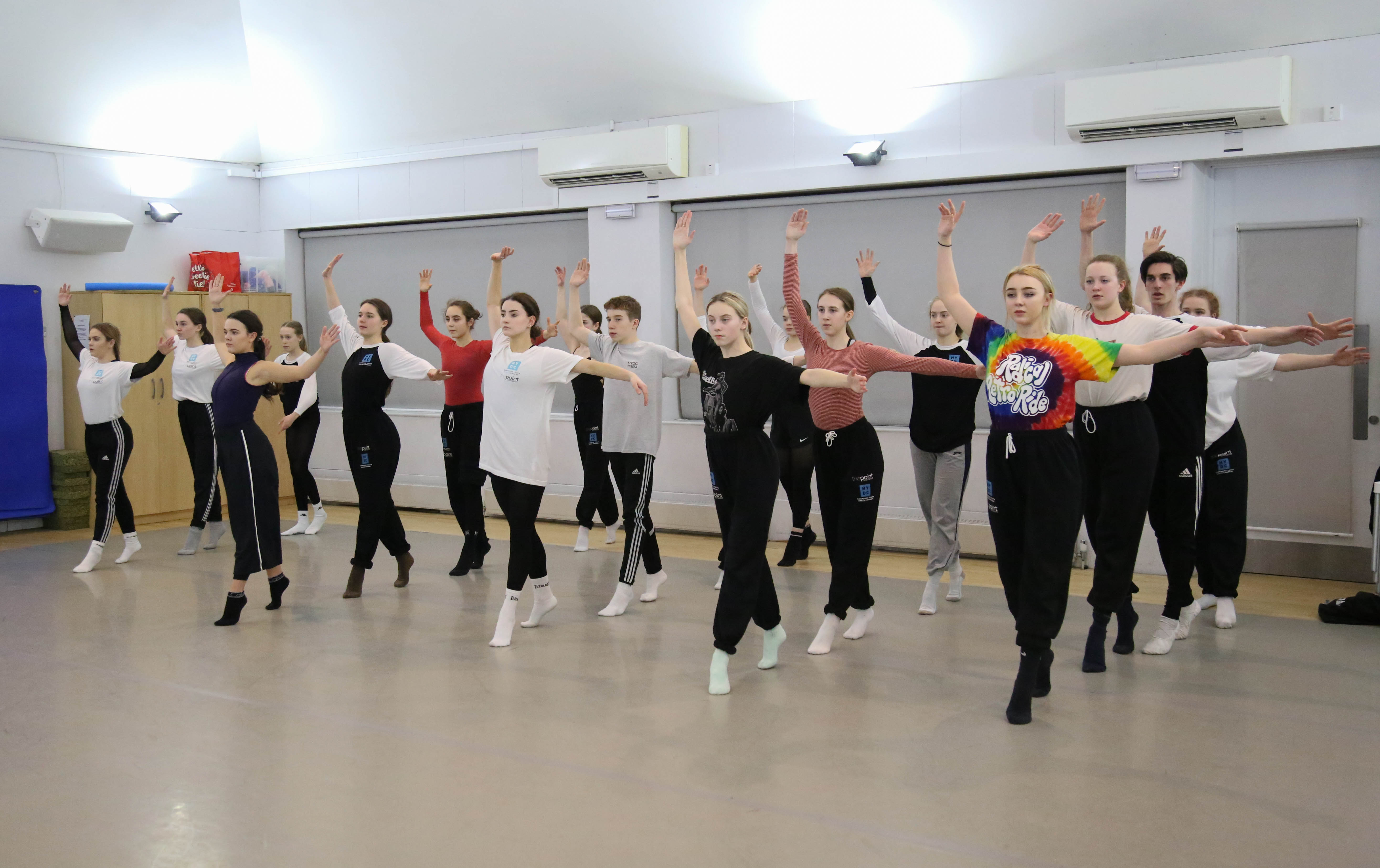 Group of young dancers of mixed genders in synchronisation during a class rehearsal in the dance studio