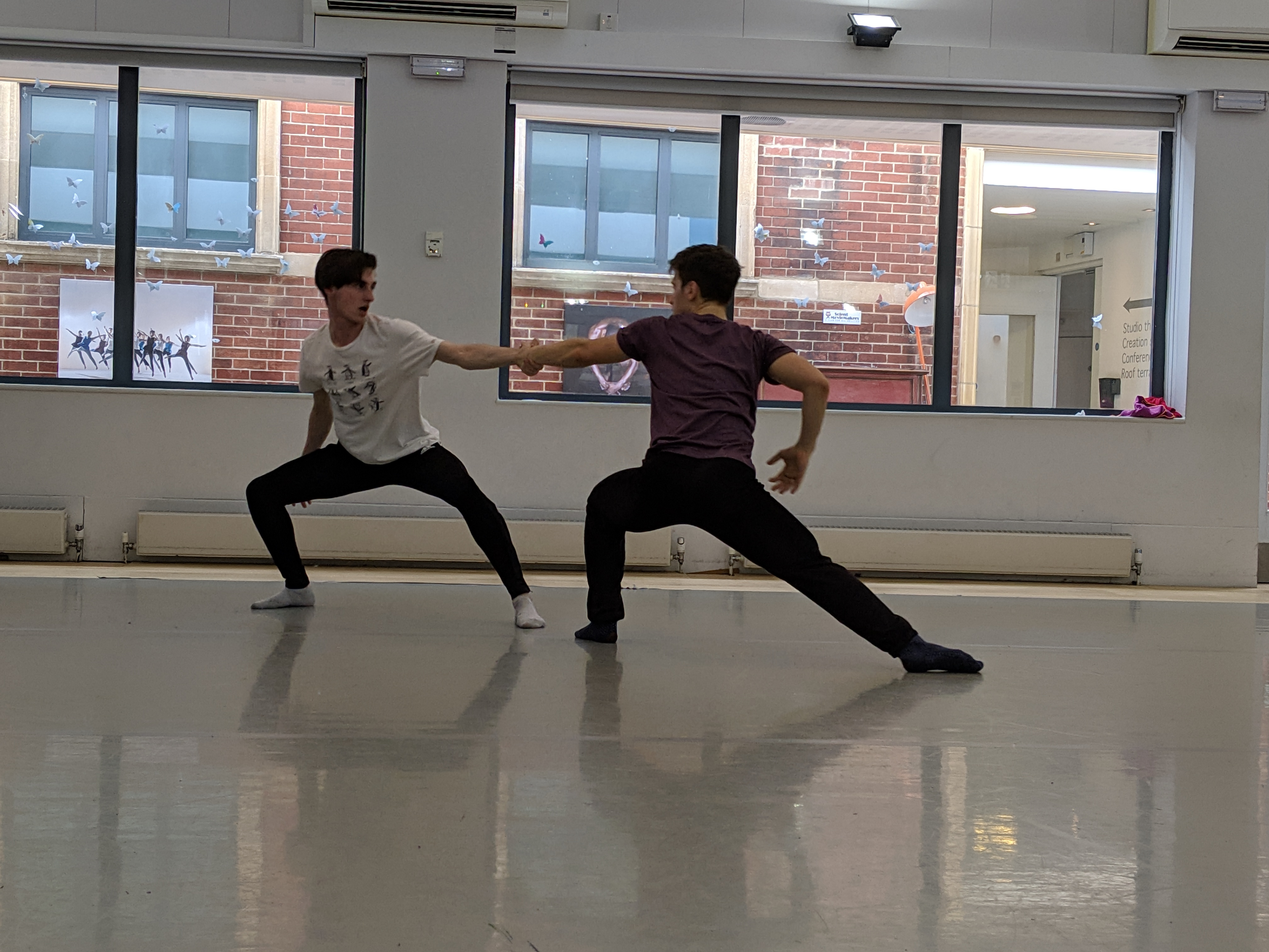 Two male dancers during a class in the dance studio with window to the atrium in background