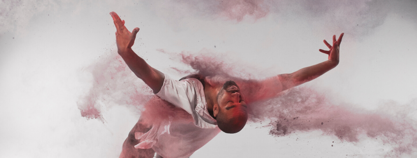 one contemporary male dance performer leaning right back from the waist with clouds of coloured dust erupting around them