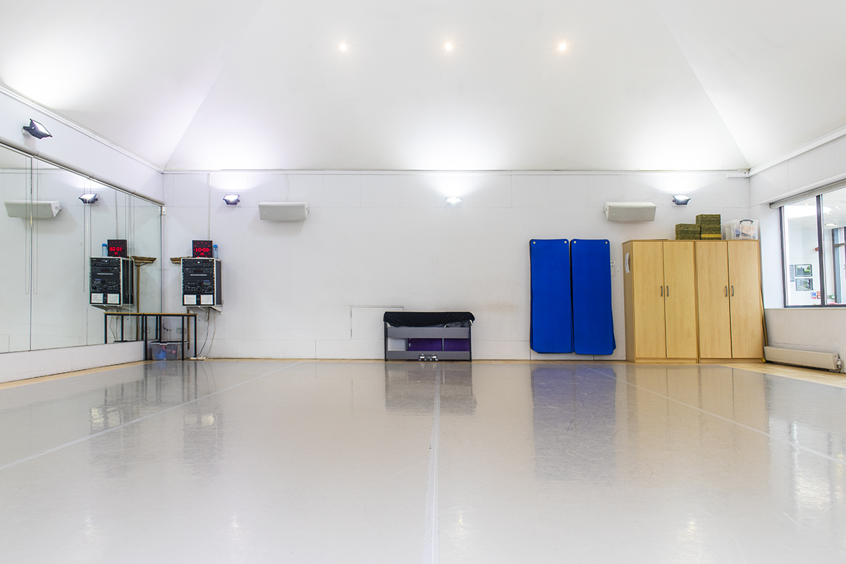 Empty dance studio facing towards sound system and storage cupboards
