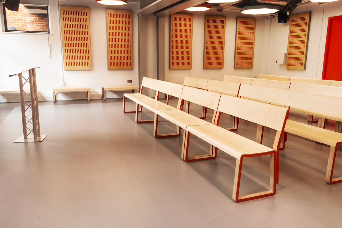 Empty studio theatre bench seating arranged in straight rows with lectern at the front
