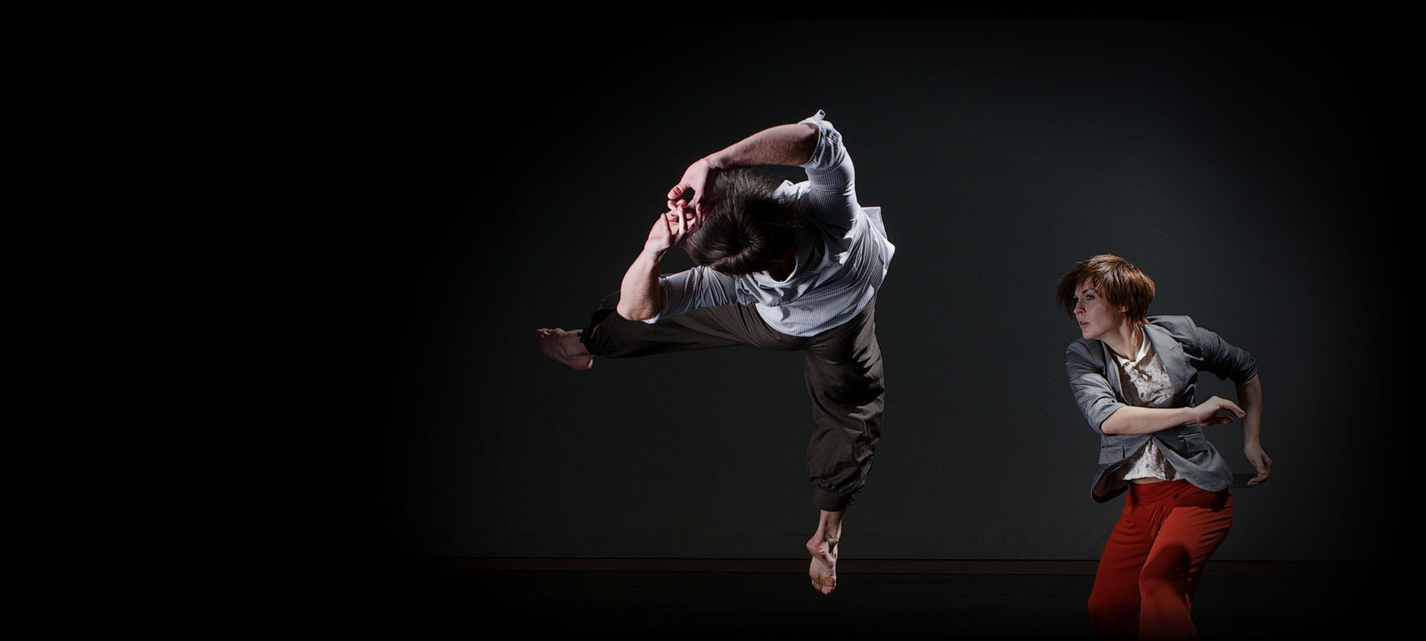 Two contemporary dancers mid movement, one leaping backwards, both legs in the air, arms behind head. The other set to leap.